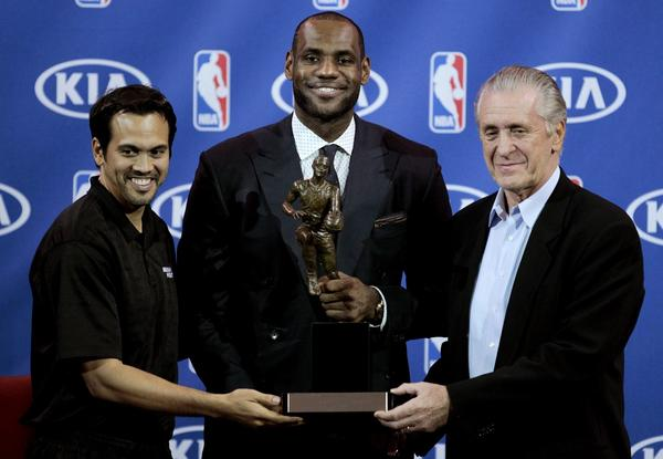 Miami Heat forward LeBron James (C) holds the trophy as he stands with head coach Erik Spoelstra (L) and team president Pat Riley, after being named NBA Most Valuable Player at a ceremony in Miami May 5, 2013. It was the fourth time in five years that the 28-year-old James had won the game's most prestigious individual award, elevating him among the sport's greatest players. The Heat meet the Chicago Bulls in Game 1 of the NBA basketball Eastern Conference semi-finals in Miami on May 6. REUTERS/Joe Skipper (UNITED STATES - Tags: SPORT BASKETBALL PROFILE) ORG XMIT: JLS01
