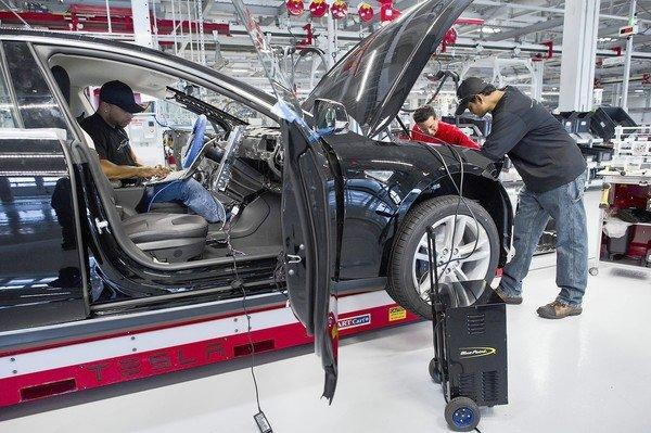 The state's Air Resources Board has mandated that zero-emission vehicles comprise 15% of new-car sales by 2025 — up from less than 1% now. Above, Tesla employees work on a Model S electric car at the company's factory in Fremont, Calif.