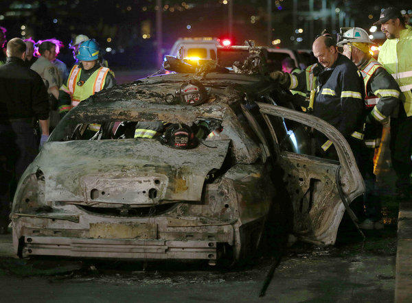 San Mateo County firefighters and California Highway Patrol personnel investigate the scene of a deadly limousine fire on the westbound side of the San Mateo-Hayward Bridge in Foster City, Calif.