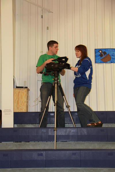 Lori Goldade, right, Warner School technology coordinator, talks to senior Levi Dinger about how to use the live streaming equipment donated by the Warner School Foundation.