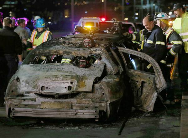 San Mateo County firefighters and California Highway Patrol personnel examine a limousine that was engulfed in flames Saturday night on the San Mateo-Hayward Bridge. Five women were killed and four others were injured, two critically. The driver was not hurt.