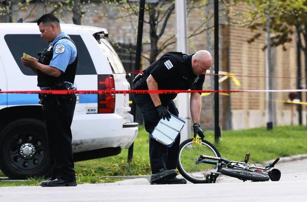 A member of the Chicago Police Department puts a marker down during a shooting investigation at the corner of 13th Street and S. Independence Blvd.