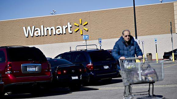 Customer Joel Merrill pushes a shopping cart outside a Wal- Mart store in East Peoria.