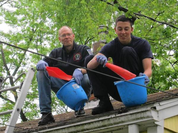 Firefighter/Paramedic Paul Roscoe, left, and former Fire Explorer Mick LoMastro, right, team up to clear a resident's gutters of winter debris during the A-May-Zing Mundelein event.