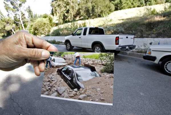 Local resident Gilbert Jacobi, who is happy to have K-rails in front of his home in the 5400 block of La Forest Drive, shows photos of his cars that were covered by mudflows during the 2010 storms.