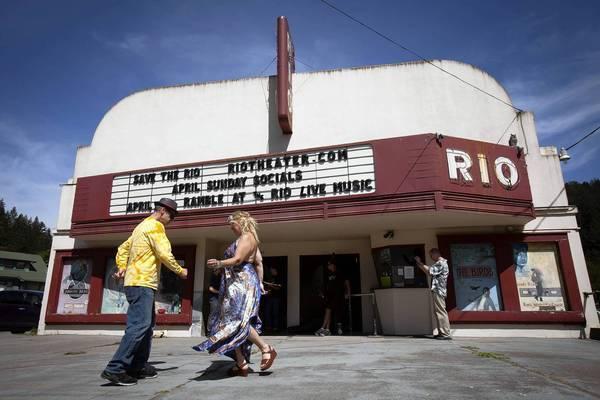 Robert Neir and Sage O'Connell dance to bluegrass music in front of the Rio Theater in Monte Rio, Calif., as musicians practice before a concert to raise funds for the historic theater.