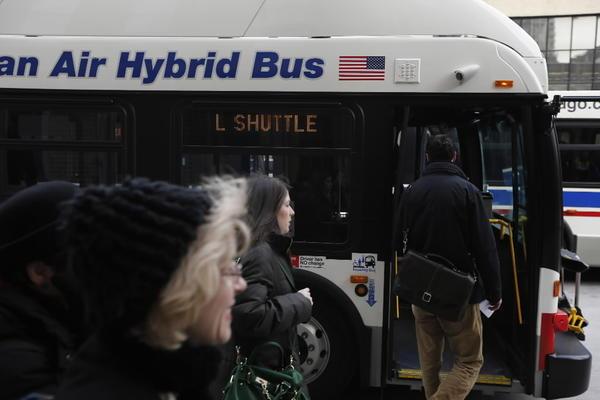 Commuters board a CTA Brown Line shuttle bus Saturday.