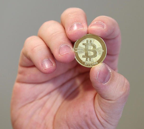 Software engineer Mike Caldwell shows the front of a physical Bitcoin he minted in his shop on April 26, 2013 in Sandy, Utah. Bitcoin is an experimental digital currency used over the Internet that is gaining in popularity worldwide.