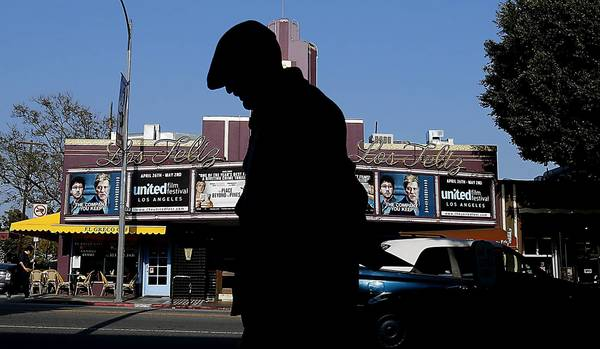 "A pedestrian walks past the Los Feliz Theater on Vermont Avenue, a landmark of Los Angeles' Los Feliz neighborhood. No one can seem to agree if using the Spanish pronunciation (Los Fey-LEASE) is respectful — or pretentious. One resident says most still anglicize the neighborhood's name (Los FEE-lus). ""I don't think one or the other is correct,"" he said. ""I think it's a matter of understandability."""
