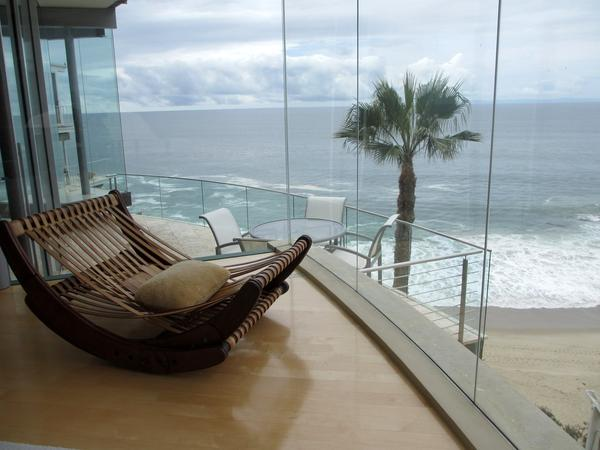 """The last stop on the Charm House Tour is the """"Floating Glass House,"""" which is perched on a cliff. The home hangs over waves crashing on the rocks below."""