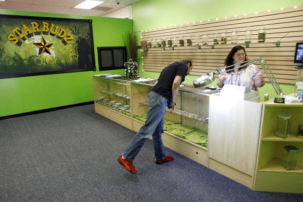 "In this May 5, 2010, photo, ""budista"" Angela Nagel assists a client at the Starbudz medical marijuana dispensary in North Hollywood. California cities and counties can ban the shops, the state's highest court ruled Monday."