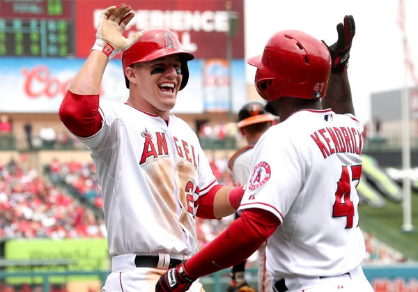 Angels' Mike Trout celebrates with Howie Kendrick after scoring a run against the Baltimore Orioles.