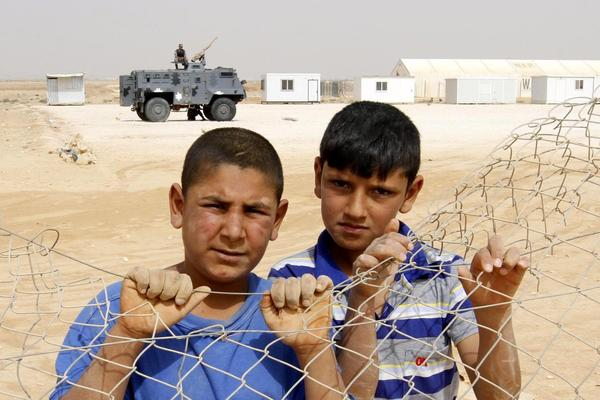 Syrian refugee children watch a soccer training session at the Syrian Zattari refugee Camp in Jordan.