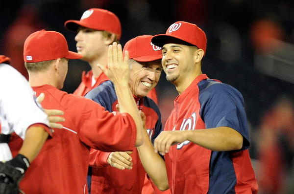 Nationals manager Davey Johnson, center, and his players celebrate after a win over the Reds.