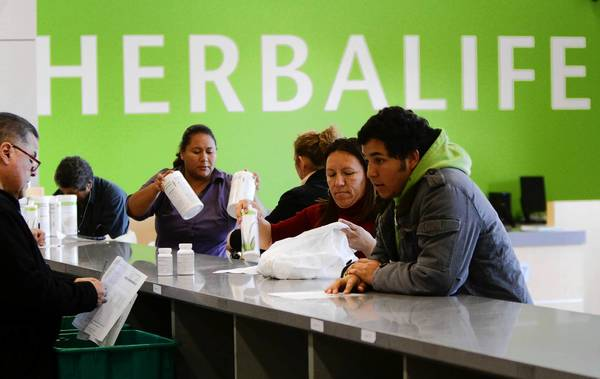 Distributors line up at the main counter at the Herbalife Distribution Center in Carson. The company says most of its distributors do not intend to make a living selling its shake mixes, vitamins and protein bars. Instead, they sign up as distributors to receive discounts on products they personally consume.