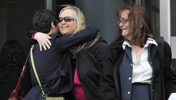 Janiece Theeke, center, hugs attorney Marni Willenson while attorney Susan Malone looks on. Theeke is among 138 women eligible to re-apply with the Chicago Fire Department following a class-action lawsuit.