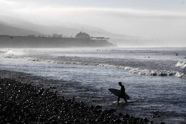 Early morning surfers catch a few waves as a fog bank clears away at Lower Trestles in San Clemente with the San Onofre Nuclear Generating Station in the background.