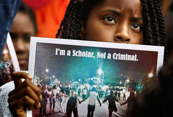 Folasade Aremu, a freshman economics major, holds a photograph during a sit-in on the campus of USC to protest the way police responded to a a weekend party near campus.