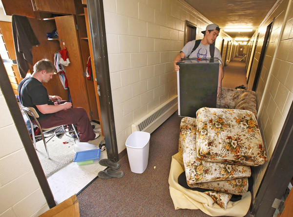 Jordan Russell of Oshkosh, Neb., left, sorts through his things as he packs while Blake Lohr of Watertown moves a dorm refrigerator past a couch in the hallway in Jerde Hall last week. The pair of freshmen were among the many Northern State University students starting to move out as the school year wrapped up.