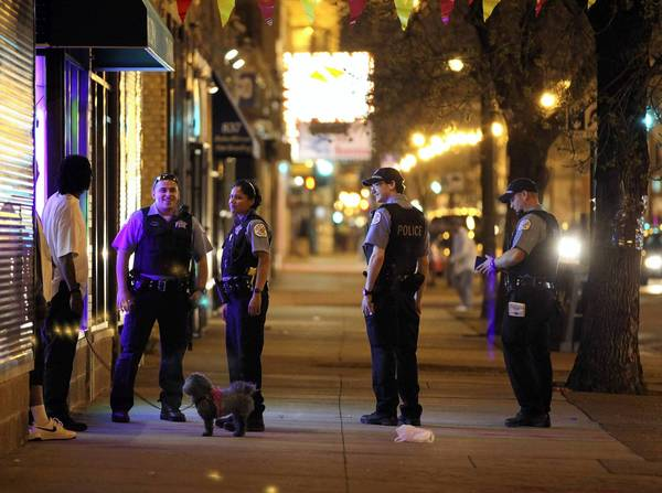 Chicago police officers on foot patrol stop to talk to a couple of men on 79th Street during an April 30 night shift.