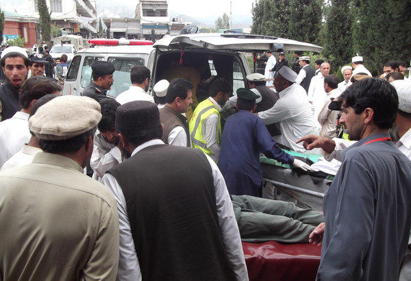 Men help injured blast victims arrive at a hospital following a bombing at an election campaign meeting in the Kurram tribal district in Pakistan on Monday. The bombing killed 25 people and wounded 70 others; bombings Tuesday claimed at least 15 more lives.