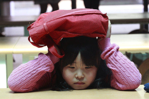 A South Korean elementary school student covers her head with a school bag at an underground shelter Tuesday during a drill for a possible airstrike at Sohwa elementary school in Paju near the border with North Korea.