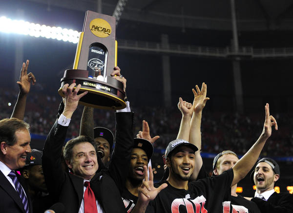 Coach Rick Pitino holds the trophy with his team after Louisville won the NCAA championship game in April.