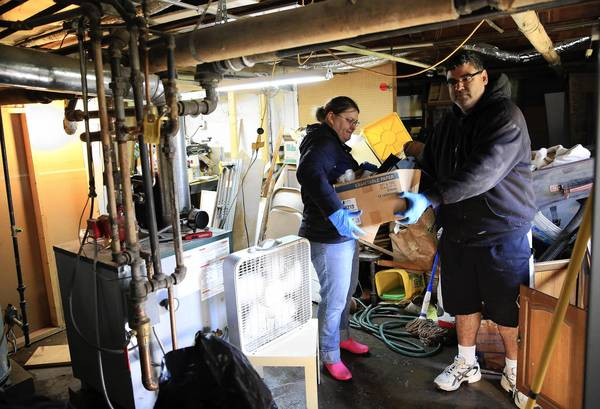 Debbie Schumacher works friend, Marcus Lugo, to clean out the water logged belongings in her mother's basement on Oakwood Avenue near White Street in Des Plaines on April 21.