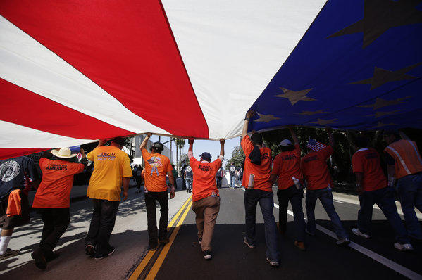 Union workers march along the street with a huge American flag during a May Day rally in Los Angeles.