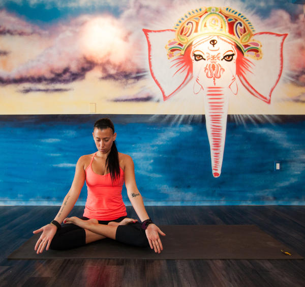 "Gabby Levine, owner of Ritual Yoga Arts in Laguna Beach, strikes a simple yoga pose. The Ganesh elephant head in the background was painted by Laguna street artist Bandit. The deity is revered as the ""remover of obstacles."""