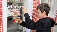 Dominik, 9, fills a cup with frozen yogurt