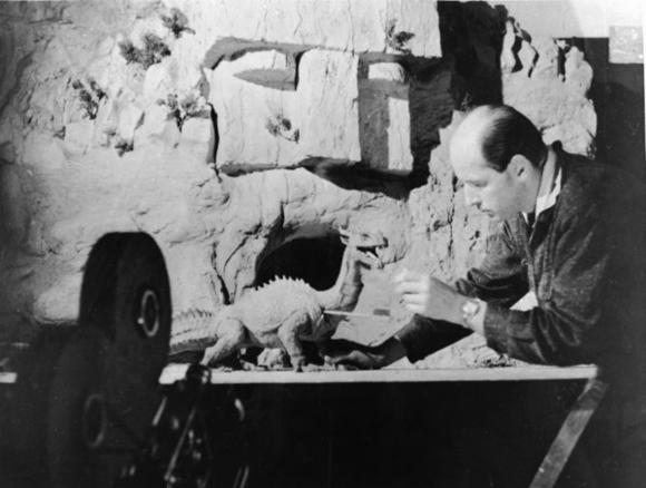 "Ray Harryhausen, best known for his stop-motion animation in ""Jason and the Argonauts"" and ""Clash of the Titans,"" works with a figure of a dinosaur as a camera rolls in 1965."
