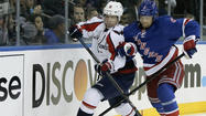Washington Capitals center Backstrom and New York Rangers defenseman Stralman chase puck in first period of Game 3 of their NHL Stanley Cup playoffs Eastern Conference quarterfinal hockey game in New York
