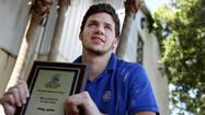 Orlando Christian Prep 3-sport athlete Mikey Walmer is shown with the school's Male Athlete of the Year award he received Monday night, 3 days after an accident in which he was thrown 65 feet from his truck. Walmer sustained no broken bones. (Jacob Langston, Orlando Sentinel)