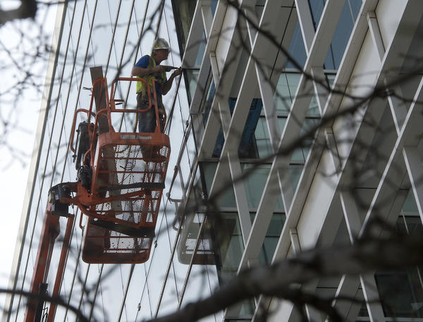 A worker installs retainers on the window openings for the Butz Corporate Center last month. Alvin H. Butz has announced the first two tenants for Phase II of its expanded downtown Allentown office building.