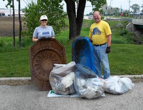Volunteers from the 2011 DuPage River cleanup event pose with some of the garbage they pulled out of Plainfield's waterways.