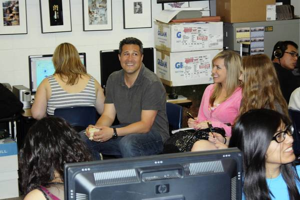 Maine West teacher Gregory Regalado looks up as media and colleagues enter his classroom to inform him of his award.