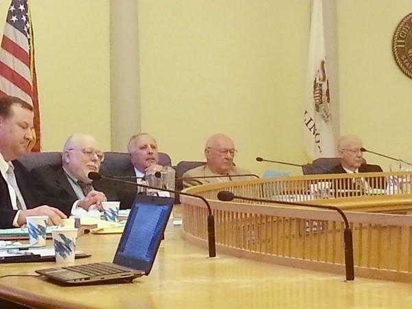 """Park Ridge Ald. Richard DiPietro, center, listens to debate before taking his final vote after 18 years on the city council. From left to right are Alds. Sal Raspanti (who also stepped down from the council), Jim Smith, DiPietro, Joseph Sweeney, and City Attorney Everette """"Buzz"""" Hill."""