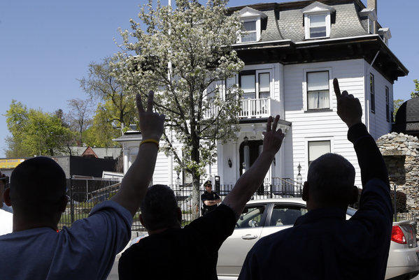 Protesters gesture outside the Graham, Putnam, and Mahoney Funeral Parlors in Worcester, Mass., where the body of killed Boston Marathon bombing suspect Tamerlan Tsarnaev is being prepared for burial.