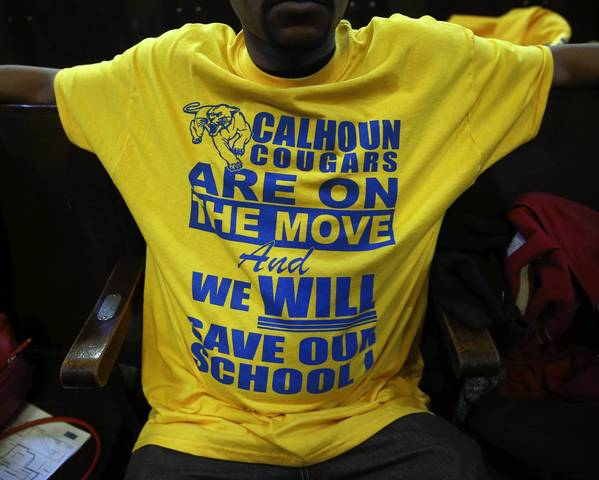A parent wears a T-shirt backing Calhoun Elementary School at a CPS meeting last month. Hearing officers oppose about a quarter of the proposed school closings.