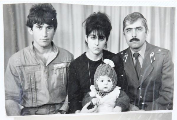 The infant Tamerlan Tsarnaev is held by his mother, Zubeidat Tsarnaeva, flanked by his father and an uncle, before the family made the move to the United States.