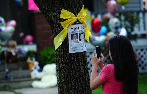 A young girl takes a picture of a missing person sign displaying portraits of amanda Berry, one of the three women held captive for a decade, stands in front of her sister's house May 7, 2013 in Cleveland, ohio. Three brothers have been arrested in connection with the kidnapping of three women found safe in a home after being missing for a decade, authorities said. There were more questions than answers the day after the stunning turn of events that began with a frantic arm sticking out of a screen door, a woman screaming for help, and a neighbor kicking in the door to free her in a working-class neighborhood of the city in the American heartland. Ariel Castro and his brothers - Pedro, 54, and Onil, 50 have been detained, authorities said.