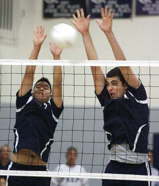 Flintridge Prep's Harrison Jung and Kareem Ismail reach for the block against Whitney in a CIF Southern Section Division IV first-round playoff boys' volleyball match at Flintridge Prep on Tuesday. (Tim Berger/Staff Photographer)