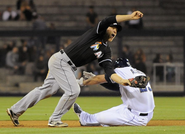 SAN DIEGO, CA - MAY 7: Chris Valaika #13 of the Miami Marlins injures his hand as he tries to tag out Yonder Alonso #23 of the San Diego Padres as he steals second base during the eighth inning of a baseball game at Petco Park on May 7, 2013 in San Diego, California. (Photo by Denis Poroy/Getty Images) ORG XMIT: 163493491