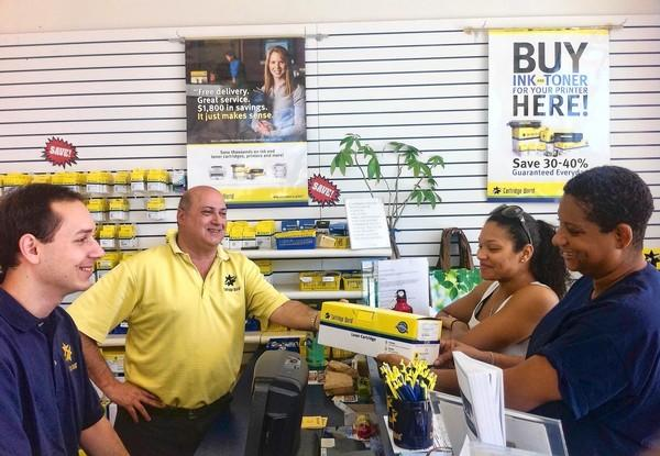 Jeffrey Rosenzweig and son Adam Rosenzweig assist customers Tanya Harris and Alicia Scott, of T's Extra Touch, at Cartridge World in Boynton Beach.