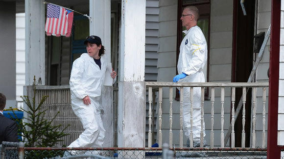 FBI forensic personnel remove evidence from the house where three women were held captive for a decade in Cleveland.