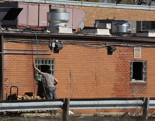 A man looks inside the fire-damaged building following an overnight fire at Myron & Phil restaurant in Lincolnwood.