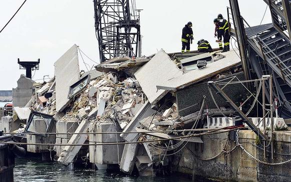 Rescue workers inspect the scene of a damaged control tower in the port of Genoa after a container ship smashed into the tower, leaving at least seven people dead and several missing in the nighttime accident.