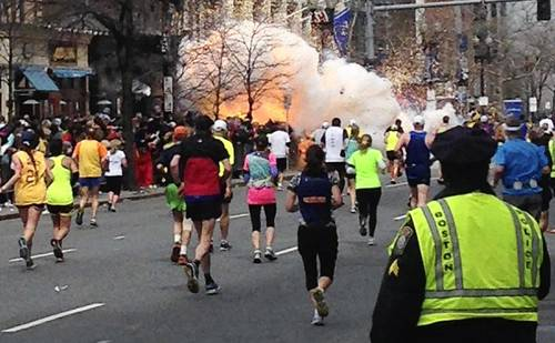Runners continue toward the finish line of the Boston Marathon on April 15, 2013, as an explosion erupts near the finish line of the race.