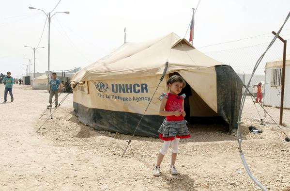 A Syrian refugee stands outside her tent at a refugee camp near the city of Mafraq, Jordan.